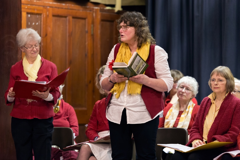 Two ladies standing on stage doing a reading