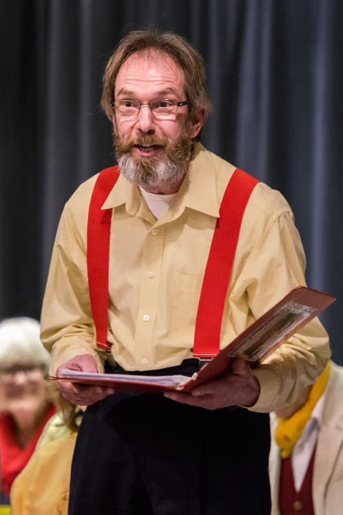 Man reading from a folder wearing a yellow shirt and red braces