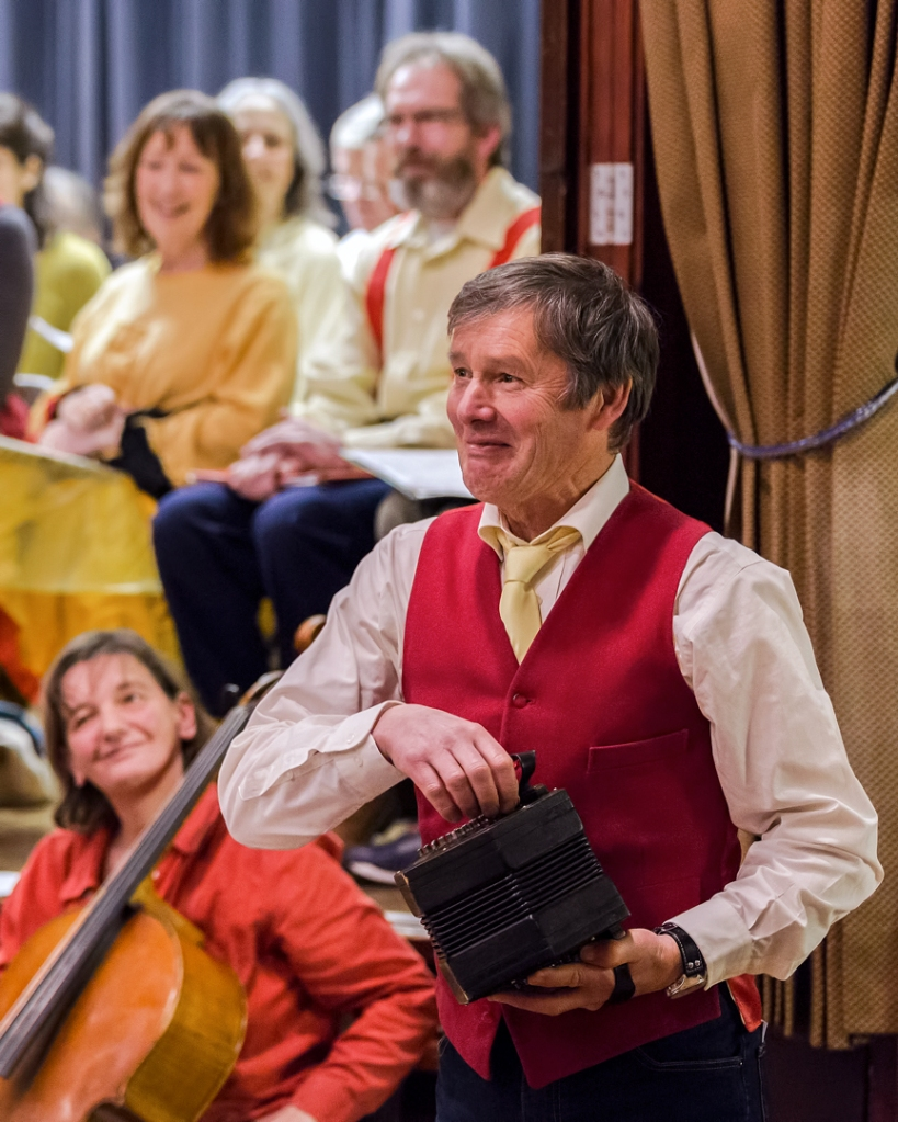 Man in red waistcoat playing a small accordian