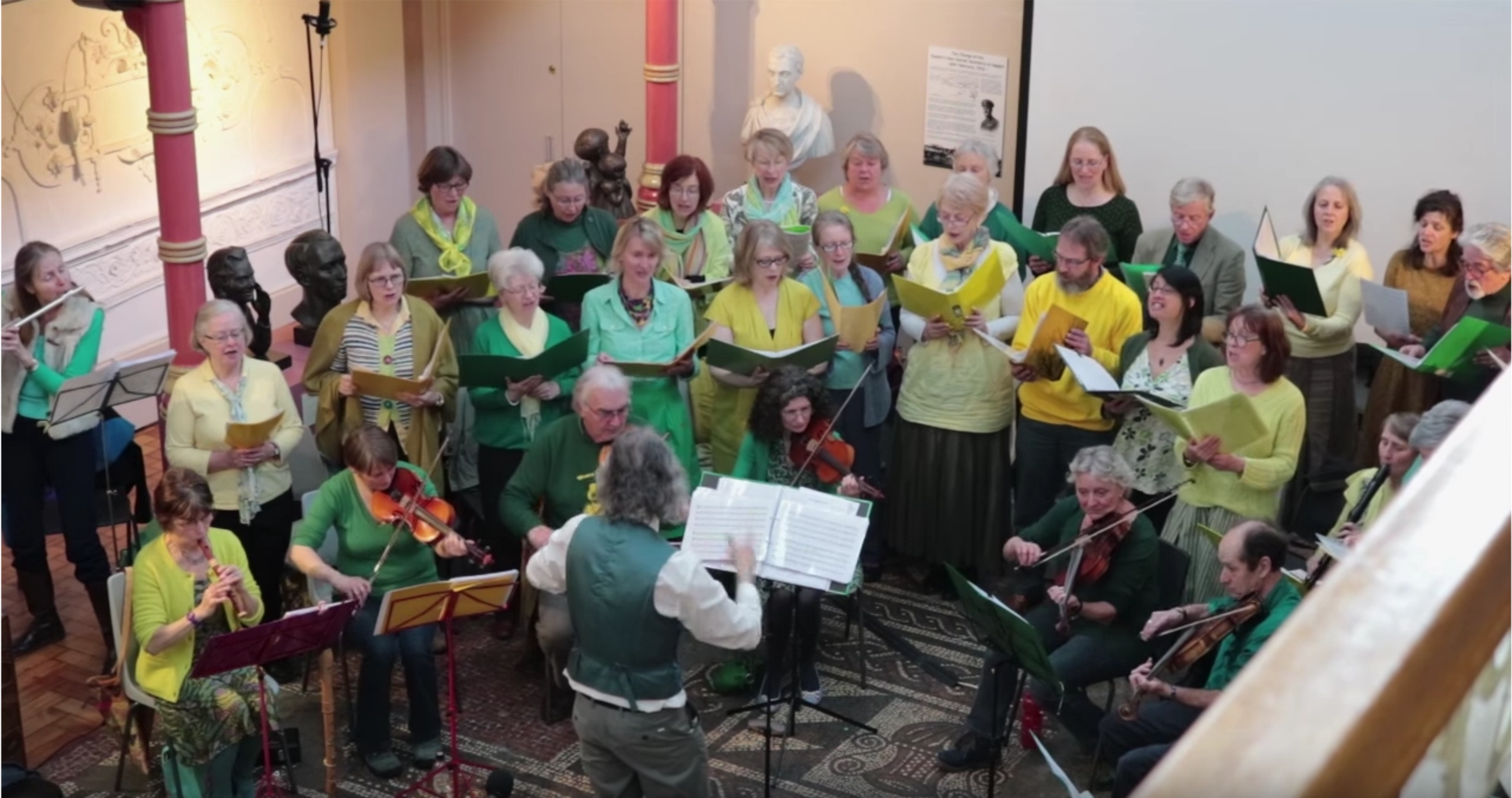 Group of singers and musicians dressed in green and yellow